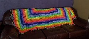 Rainbow blanket on brown couch